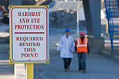 Warning sign saying 'Hardhat and Eye Protection Required Beyond This Point' at an asphalt plant
