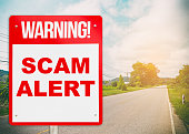 A warning sign warning about Scam in road ahead.