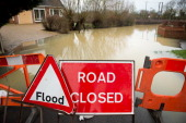 Warning signs prevent traffic entering a flooded road in Tewkesbury Gloucestershire western England on January 5 2014 Weather reports suggest further...