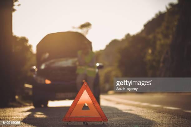 Warndreieck vor ihr kaputtes Auto