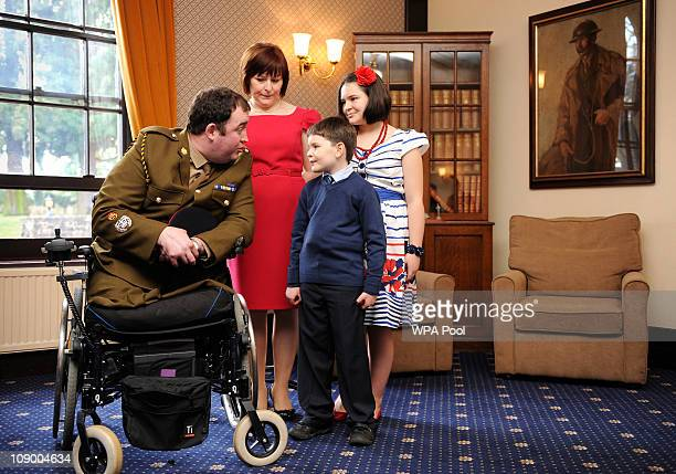 Warrant Officer Ken Bellringer speaks to his son Harry 8 alongside his wife Christine and daughter Neeve before receiving a medal from Prince Charles...
