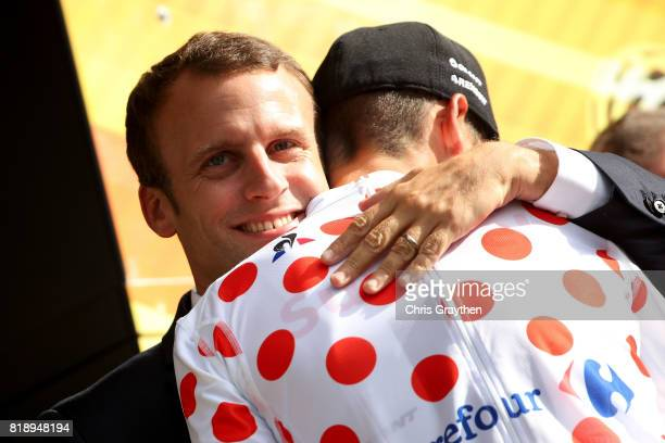 Warren Barguil of France riding for Team Sunweb stands on the podium in the king of the mountain jersey and talks with French President Emmanuel...