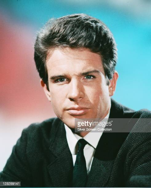 Warren Beatty US actor wearing a herringbone tweed jacket a white shirt and a black tie in a studio portrait against a red and blue background circa...