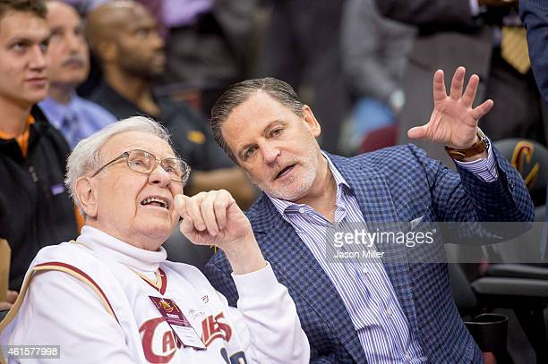 Warren Buffet talks with Cleveland Cavaliers owner Dan Gilbert the Charlotte Hornets during the second half at Quicken Loans Arena on December 15...
