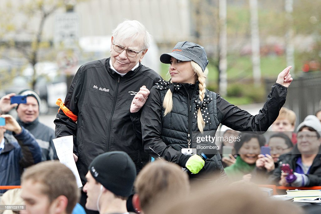 Warren Buffett, chairman and chief executive officer of Berkshire Hathaway, Inc., dances with the race emcee at the starting line of the 'Berkshire Hathaway Invest In Yourself 5K' race presented by Brooks Sports, Inc., a Berkshire company, in Omaha, Nebraska, U.S., on Sunday, May 5, 2013. Warren Buffett, the leader of Berkshire Hathaway since the 1960s, said the company's next chief executive officer will bolster the company's reputation as a source of stability in times of crisis. Photographer: Daniel Acker/Bloomberg via Getty Images