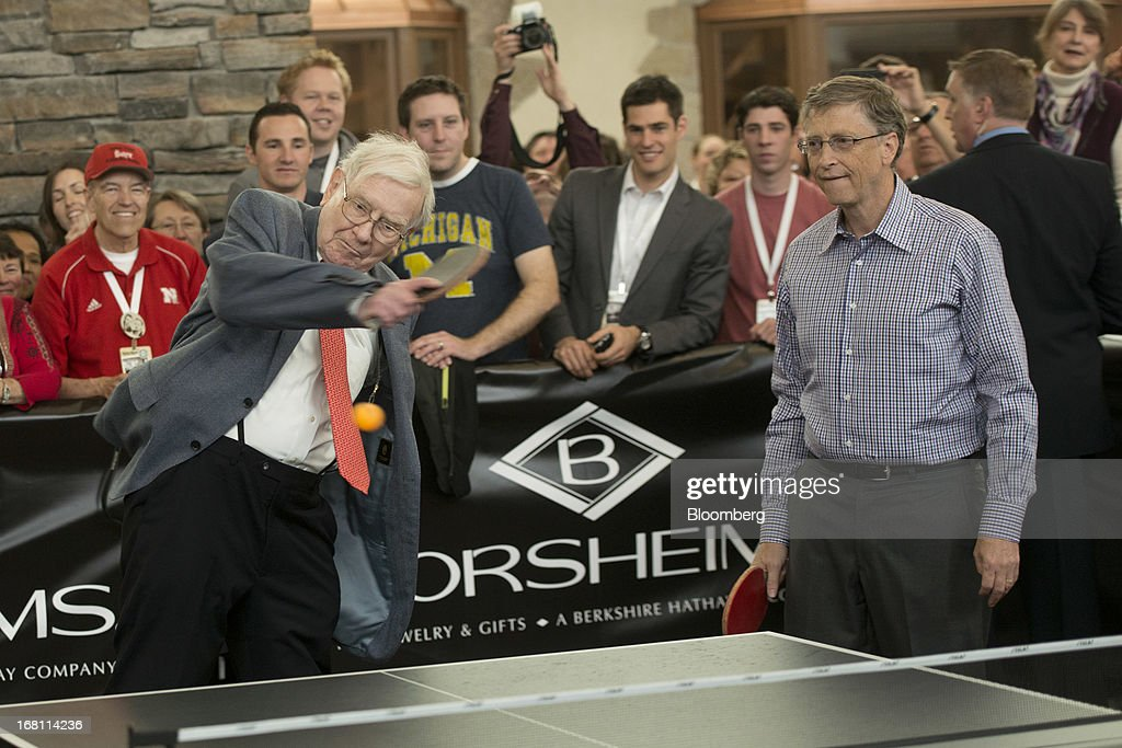 Warren Buffett, chairman and chief executive officer of Berkshire Hathaway, Inc., left, returns a ball as Bill Gates, chairman and founder of Microsoft Corp., looks on during a table tennis match outside Borsheims Jewelry Company, Inc., in Omaha, Nebraska, U.S., on Sunday, May 5, 2013. Warren Buffett, the leader of Berkshire Hathaway since the 1960s, said the company's next chief executive officer will bolster the company's reputation as a source of stability in times of crisis. Photographer: Daniel Acker/Bloomberg via Getty Images