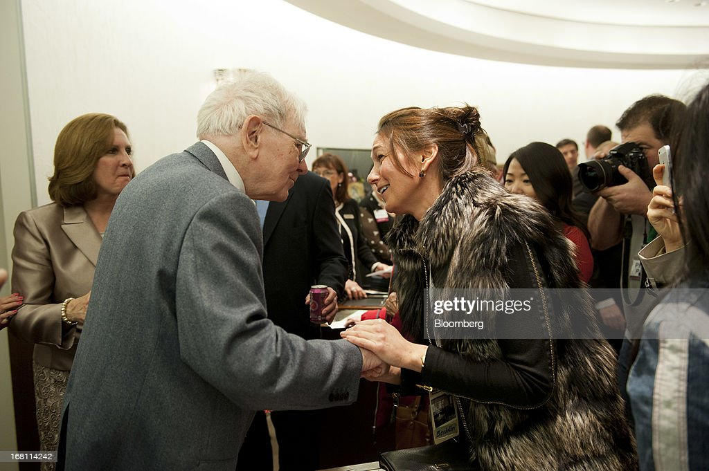 Warren Buffett, chairman and chief executive officer of Berkshire Hathaway, Inc., shakes hands with Ingrid Johnson, a Berkshire shareholder from Johannesburg, South Africa, at Borsheims Jewelry Company, Inc., in Omaha, Nebraska, U.S., on Sunday, May 5, 2013. Warren Buffett, the leader of Berkshire Hathaway since the 1960s, said the company's next chief executive officer will bolster the company's reputation as a source of stability in times of crisis. Photographer: Daniel Acker/Bloomberg via Getty Images