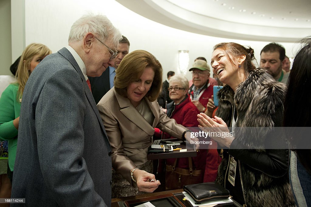 Warren Buffett, chairman and chief executive officer of Berkshire Hathaway, Inc., left, stands with Susan Jacques, chief executive officer of Borsheims Jewelry Company, Inc., center, as they close a sale with customer Ingrid Johnson, a Berkshire shareholder from Johannesburg, South Africa, right, at Borsheims in Omaha, Nebraska, U.S., on Sunday, May 5, 2013. Warren Buffett, the leader of Berkshire Hathaway since the 1960s, said the company's next chief executive officer will bolster the company's reputation as a source of stability in times of crisis. Photographer: Daniel Acker/Bloomberg via Getty Images