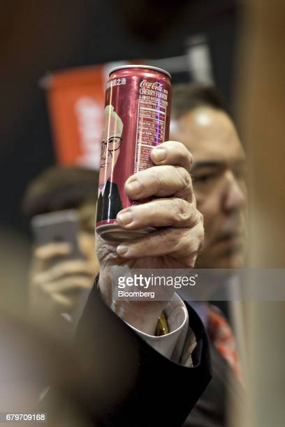 Warren Buffett chairman and chief executive officer of Berkshire Hathaway Inc holds a can of CocaCola bearing a caricature of himself as he tours the...