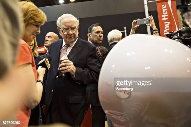 Warren Buffett chairman and chief executive officer of Berkshire Hathaway Inc second left looks at a robot in the CocaCola Co booth as he tours the...
