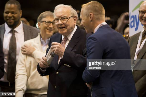 Warren Buffett chairman and chief executive officer of Berkshire Hathaway Inc center prepares to toss a newspaper at a Clayton Homes Inc display on...