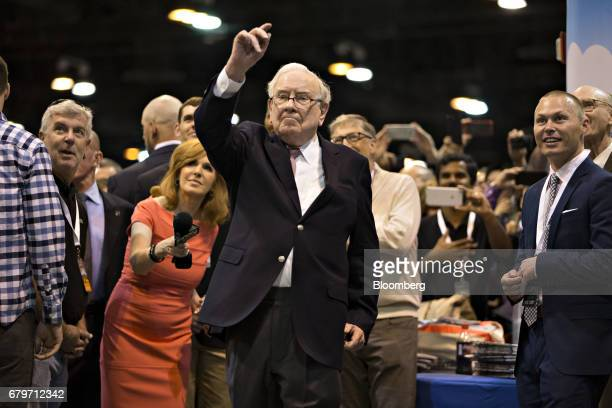 Warren Buffett chairman and chief executive officer of Berkshire Hathaway Inc throws a newspaper at the Clayton Homes Inc display during a tour of...