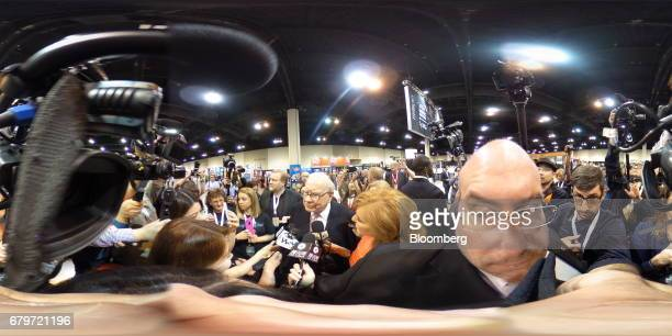Warren Buffett chairman and chief executive officer of Berkshire Hathaway Inc center speaks with members of the media on the exhibit floor ahead of...