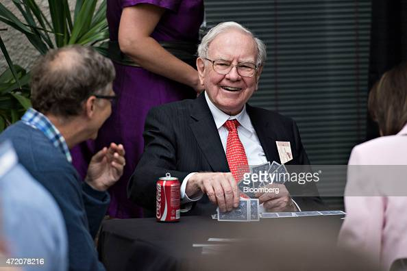 Warren Buffett chairman of Berkshire Hathaway Inc center laughs with Bill Gates chairman and founder of Microsoft Corp and a Berkshire Hathaway Inc...