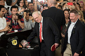 Warren Buffett chairman of Berkshire Hathaway Inc center reaches for ping pong balls during a shareholder event on the sidelines of the Berkshire...