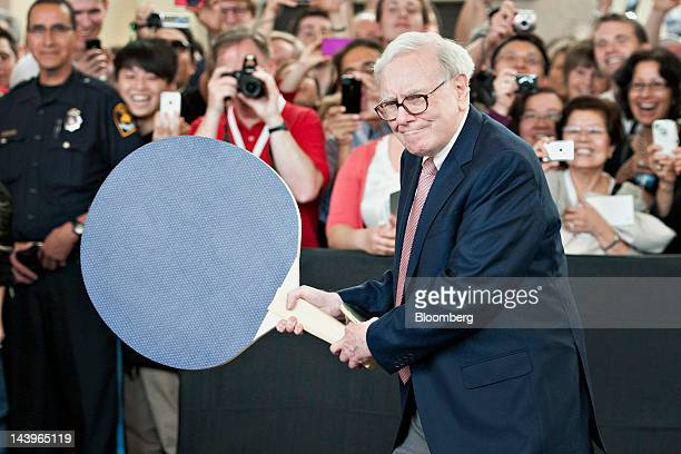 Warren Buffett chairman of Berkshire Hathaway Inc holds a large ping pong paddle as he plays table tennis with Ariel Hsing a member of the 2012 US...