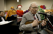 Warren Buffett chairman of Berkshire Hathaway plays the ukulele for a crowd of shareholders at the Fruit of the Loom booth during the Berkshire...
