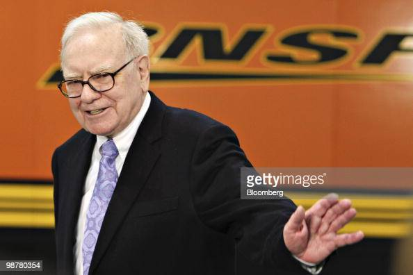 Warren Buffett chief executive officer of Berkshire Hathaway walks past a Burlington Northern Santa Fe Corp display as he tours the exhibition floor...