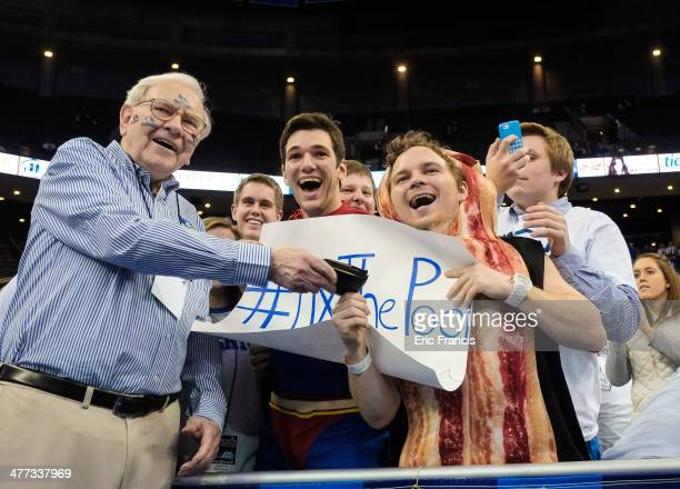 Warren Buffett of Berkshire Hathaway poses with Creighton Bluejay fans before the game between the Creighton Bluejays and the Providence Friars at...
