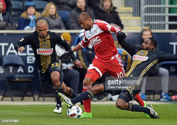 Warren Creavalle of Philadelphia Union slides to kick the ball away from Teal Bunbury of New England Revolution as Fabinho looks on at Talen Energy...