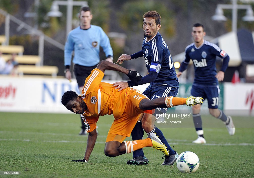 Warren Creavalle #5 of the Houston Dynamo battles for the ball with Jun Marques Davidson #27 of the Vancouver Whitecaps FC during the first half of a game on February 20, 2013 in Charleston, North Carolina.