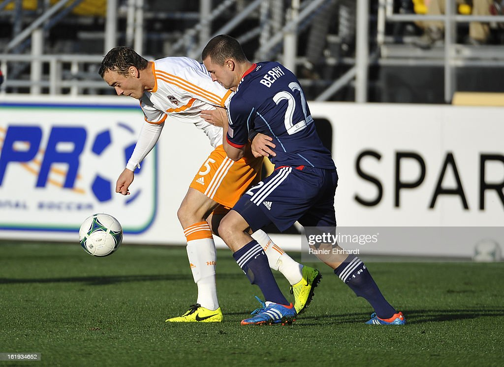 Warren Creavalle #5 of the Houston Dynamo battles for the ball with Austin Berry #22 of the Chicago Fire during the first half of their game at Blackbaud Stadium on February 16, 2013 in Charleston, South Carolina.
