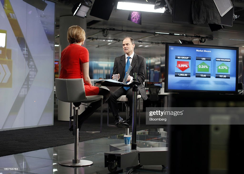 Warren East, chief executive officer of ARM Holdings Plc, right, speaks during a Bloomberg Television interview in London, U.K., on Tuesday, Feb. 5, 2013. ARM Holdings Plc, whose chip designs power Apple Inc.'s iPhone and iPad, reported fourth-quarter sales that rose more than analysts predicted as demand for smartphones and tablets surged. Photographer: Simon Dawson/Bloomberg via Getty Images
