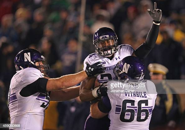 Warren Long of the Northwestern Wildcats celebrates with Matt Frazier and Brandon Vitabile after scoring on a twopoint conversion against the Notre...
