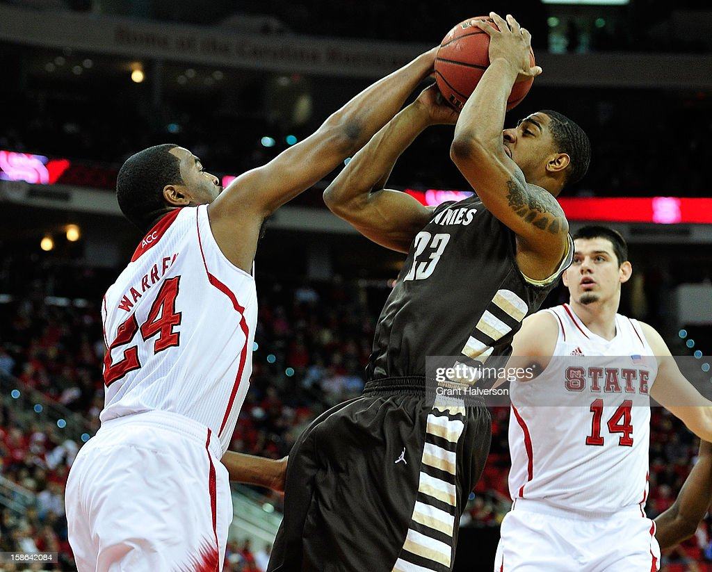 T.J. Warren #24 of the North Carolina State Wolfpack blocks a shot by Marquise Simmons #33 of the St. Bonaventure Bonnies during play at PNC Arena on December 22, 2012 in Raleigh, North Carolina.