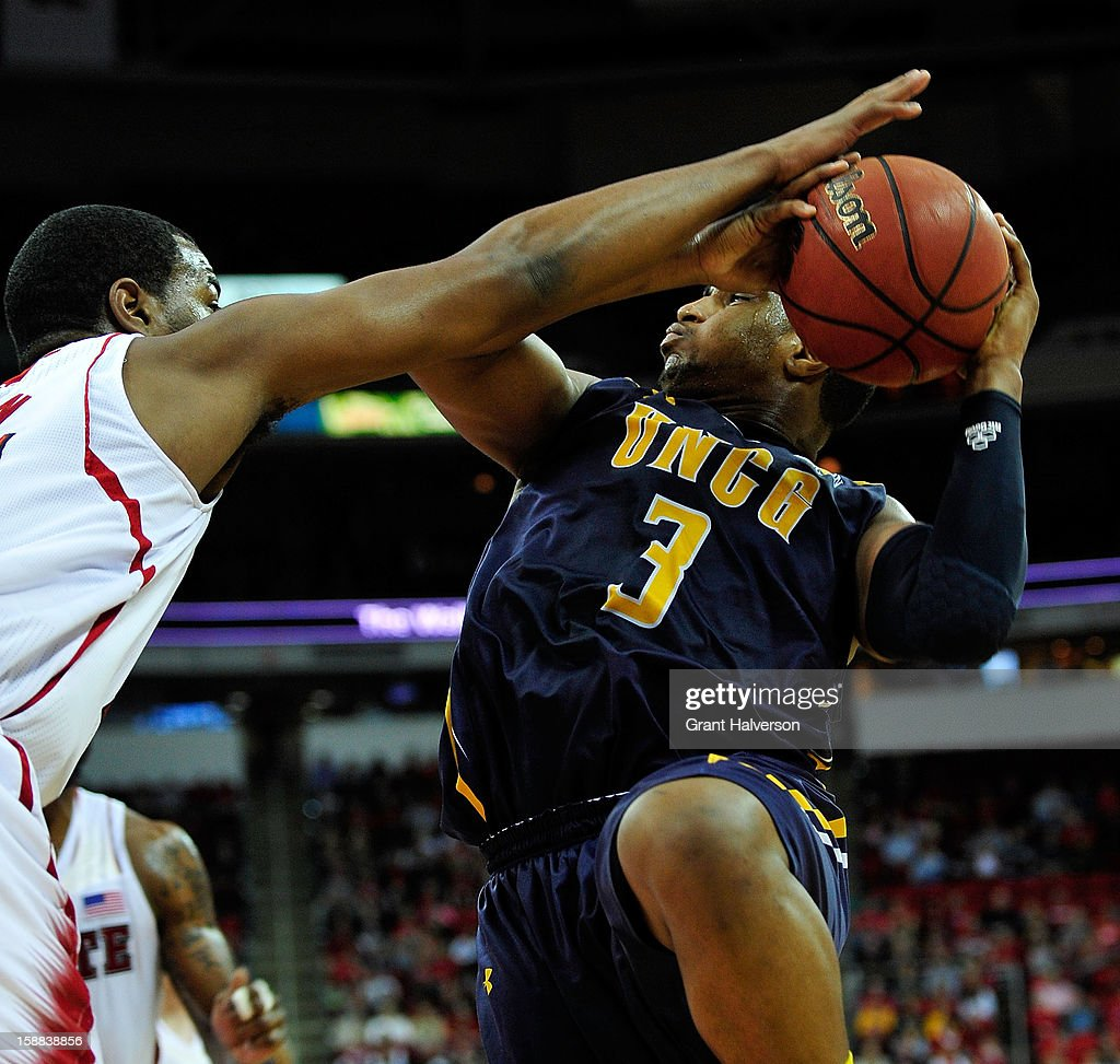 T.J. Warren #24 of the North Carolina State Wolfpack challeges a shot by Derrell Armstrong #3 of the UNC Greensboro Spartans during play at PNC Arena on December 31, 2012 in Raleigh, North Carolina.