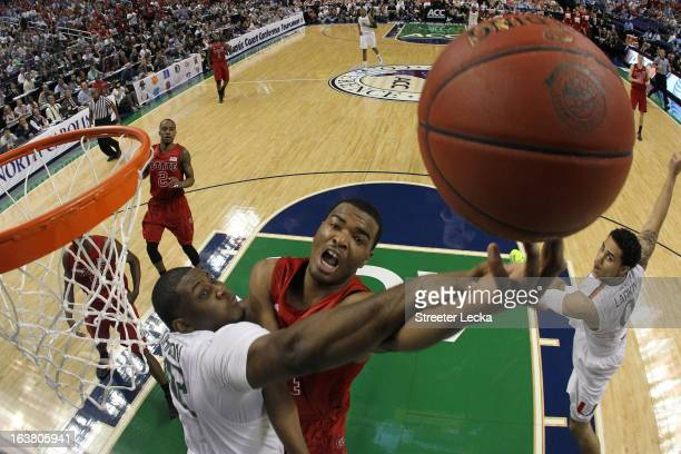 J Warren of the North Carolina State Wolfpack goes up for a shot against Reggie Johnson of the Miami Hurricanes during the men's ACC Tournament...
