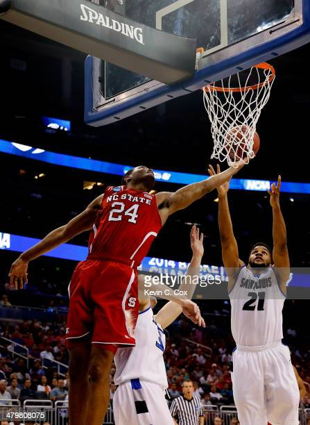 J Warren of the North Carolina State Wolfpack shoots in the first half against Jake Barnett and Dwayne Evans of the Saint Louis Billikens against...