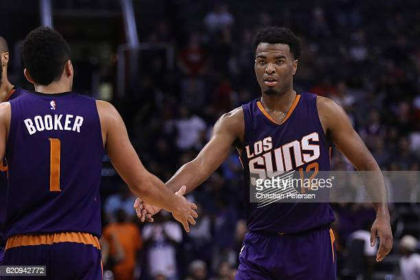 Warren of the Phoenix Suns high fives Devin Booker after scoring against the Portland Trail Blazers during overtime of the NBA game at Talking Stick...
