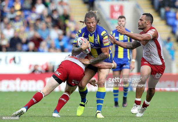 Warrington Wolves' Ashton Sims is tackled by Catalans Dragons' Remi Casty and Paul Aiton during the Betfred Super League match at the Halliwell Jones...
