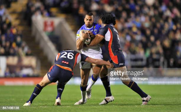 Warrington Wolves Ryan Atkins is tackled by St Helens Sia Soliola and Josh Jones during the Stobart Super League match at the Halliwell Jones Stadium...