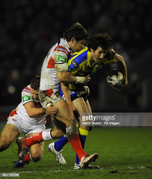Warrington Wolves' Stefan Ratchford is tackled by St Helens Louie McCarthyScarsbrook and Josh Jones during the Super League match at Halliwell Jones...