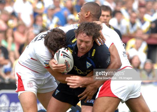 Warrington's Mike Wainwright tackled by St Helen's Jon Wilkin and Leon Pryce during the Challenge Cup Quarter Final match at Knowsley Road St Helens