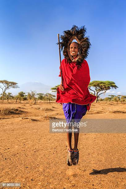 Warrior from Maasai tribe performing traditional jumping dance, Kenya, Africa