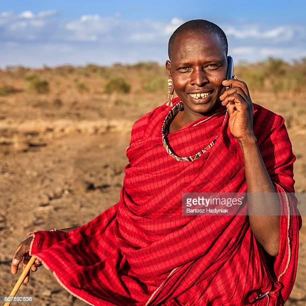 Warrior from Maasai tribe using mobile phone, Kenya, Africa