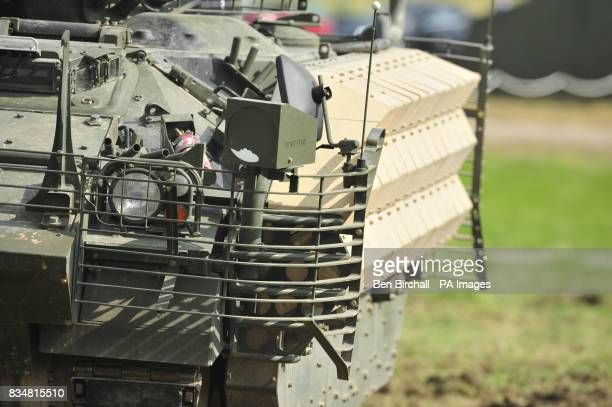 A Warrior tank with Enhanced Armour fitted in the form of heavy duty metal grids and sections that are covered in sheet steel causing antitank...