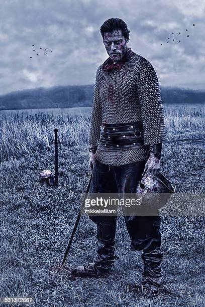Warrior with sword alone on battlefield after a fight