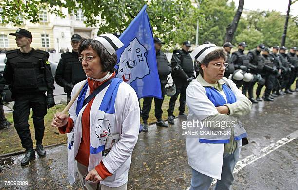 Two nurses stand near a riot police line opposite the cabinet office in Warsaw 06 July 2007 Some 2200 people demonstrated outside the seat of the...