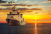 The military ship on sea at sunrise.