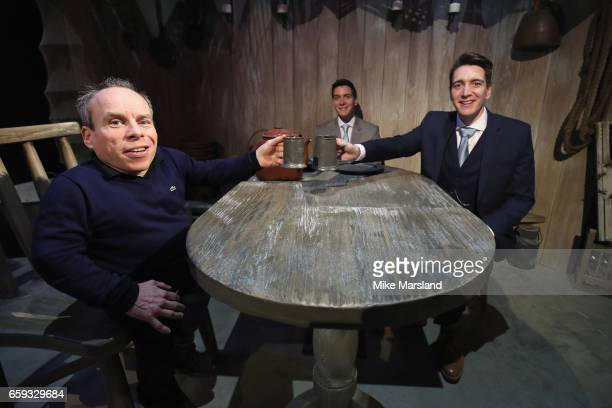 Warwick Davis Oliver Phelps and James Phelps sit at Hagrid's forced perspective table within the Forbidden Forest at Warner Bros Studio Tour London –...