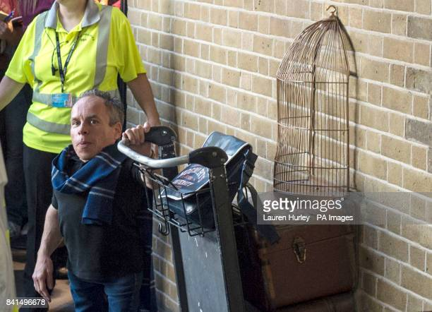 Warwick Davis who played Professor Flitwick in the Harry Potter films poses with the Platform 9 and 3/4 trolley in King's Cross Station London Today...