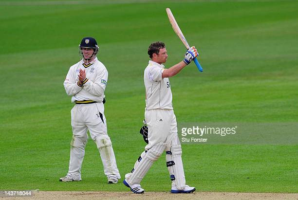 Warwickshire batsman Ian Bell celebrates after reaching his century as Durham fielder Will Smith applauds during day two of the LV County...