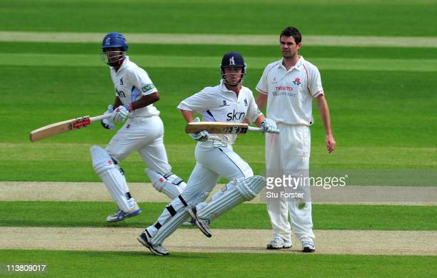 Warwickshire batsman Varun Chopra and Jonathan Trott pick up some runs as bowler James Anderson looks on during day three of the Division One LV...