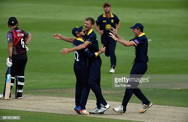 Warwickshire fielders Laurie Evans and Rikki Clarke congratulate bowler Oliver HannonDalby after he had trapped Somerset batsman Jim Allenby lbw...