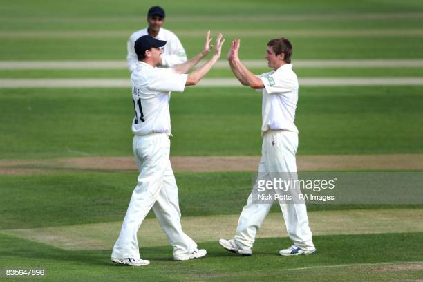 Warwickshire's Chris Woakes celebrates with Ricki Clarke after his caught and bowl of England captain Andrew Strauss during a friendly match at...