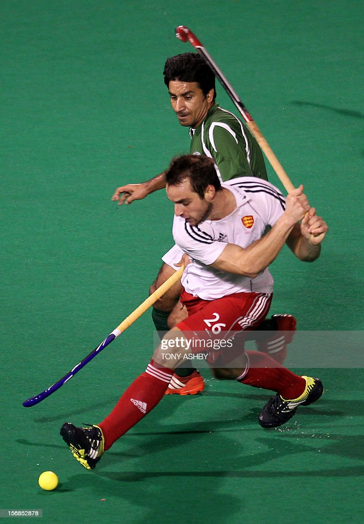 Waseem Ahmed of Pakistan (top) and Nicholas Catlin (front) of England battle for the ball during their men's match on day two at the International Super Series hockey tournament in Perth on November 23, 2012. AFP PHOTO/Tony ASHBY RESTRICTED